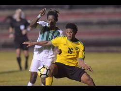 Jamaica's Nicque Daley (right) shields the ball from Dominican defender Jolly Fitz during their CONCACAF U-23 Qualifier at the Anthony Spaulding Sports Complex in Kingston on July 17.