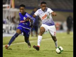 Cardel Benbow (left) of Mount Pleasant and Emelio Rousseau of Portmore United in a tussle in a Red Stripe Premier League semi-final at the National Stadium in Kingston on  April 15, 2019.