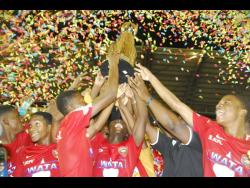 Members of the Cornwall College football team  celebrate with the ISSA Champions Cup after they clipped Jamaica College 1-0 in last season's final at the Montego Bay Sports Complex.