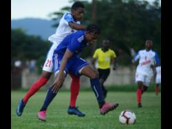 Mount Pleasant's Suelae McCalla shields the ball from Portmore United's Courtney Allen during their Red Stripe Premier League match at the Spanish Town Prison Oval yesterday.