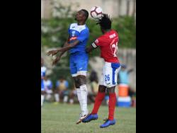 Portmore United's Cory Burke (left) goes up for a header with Dunbeholden's Shaquille Dyer during their Red Stripe Premier League encounter at the Spanish Town Prison Oval on Sunday, December 1, 2019.