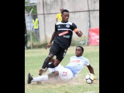 Emelio Rousseau (right) of Portmore United puts in a sliding challenge on Chevone Marsh of Cavalier during a Red Stripe Premier League match on Sunday, February 10, 2019.