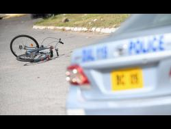 A police service vehicle is parked near the crime scene where a pedal cyclist was shot and killed by gunmen a few feet from the entrance to the Nannyville Health Centre in the Corporate Area.