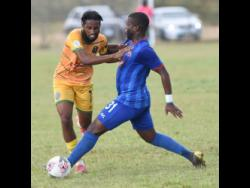Vere United's Christopher Randall (left) runs into a tackle from Rodave Murray (right) of Dunbeholden FC in their Red Stripe Premier League football match yesterday.