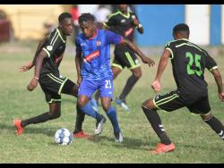 Dunbeholden's Nickoy Christie  (centre) dribbes past Molynes United's Jermey Nelson (left) and his teammate Orane Ferguson (right)  during their Red Stripe Premier League game in December last year.