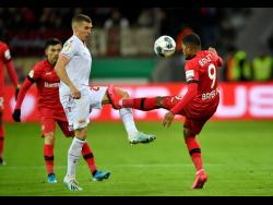 Bayer Leverkusen's Leon Bailey (right) and Union's Grischa Proemel challenge for the ball during the German Cup, DFB Pokal, quarter-final match in Leverkusen, Germany, yesterday. Leverkusen won 3-1.