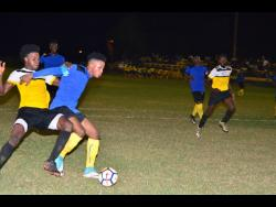 Tevoy Colespring (second left) of Meadforest FC holds off Barbican FC's Damian English during their Magnum KSAFA Super League first-round clash at the Constant Spring Complex last season.
