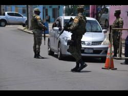 Security forces man a checkpoint along West Avenue in Greenwich Town yesterday.