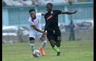 Fakibi Farquharson (right) of Molynes United dribbles by Arnett Gardens' Odane Samuels during their Red Stripe Premier League encounter at the Drewsland Stadium on Sunday, September 22.