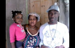 Distraught parents Shereen and Clarence Johnson stand with their four-year-old granddaugter D-Lania Arnold, whose mother, Donnia Johnson, was found dead in a male bathroom at her workplace.