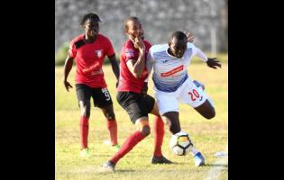 Portmore United's Rondee Smith (right) goes past Arnett Gardens' Jamar Martin in a Red Stripe Premier League encounter at the Prison Oval recently.