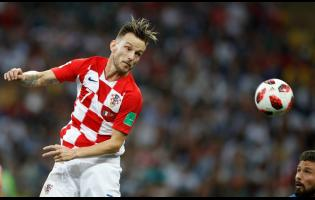 In this Sunday, July 15, 2018 file photo, Croatia's Ivan Rakitic (left) heads the ball as France's Olivier Giroud looks on during the final match of  the 2018 World Cup in the Luzhniki Stadium in Moscow, Russia.