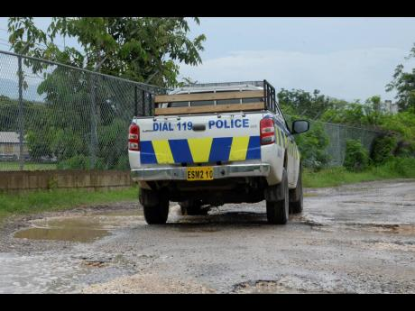 A police service vehicle manoeuvre the pothole-filled road.