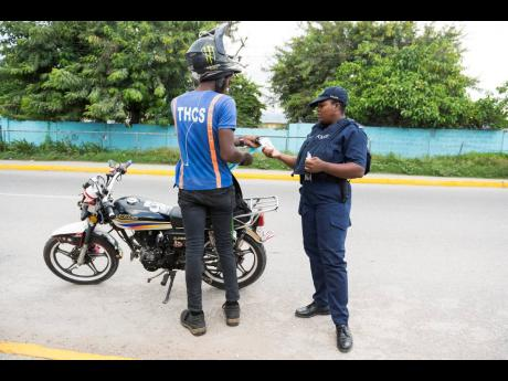 A policewoman checks the ID of a motorcycle operator along Olympic Way yesterday in the vicinity of the White Wing community.