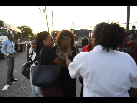 A vice-principal (centre) of Clan Carthy Primary School is consoled after the accident that took the life of Seymour Benjamin.