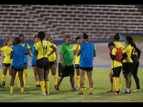 Reggae Girlz head coach Hue Menzies interacts with the team during a training session held at the National Stadium on Monday, May 13, 2019.
