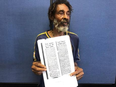 Lynden Minott with an article written about his father's death penalty.