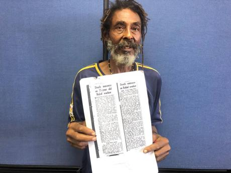 Lynden Minott with an article about his father's death penalty.