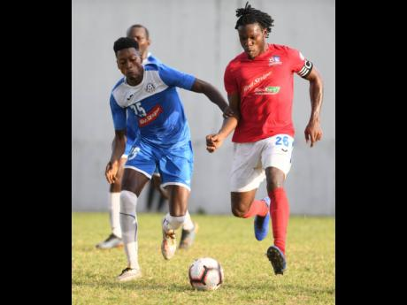 Portmore United's Shai Smith challenges Dunbeholden's Shaquille Dyer for the ball during their Red Stripe Premier League match yesterday.