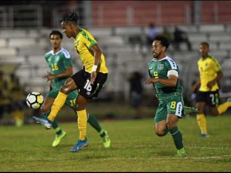 Jamaica's Peter-Lee Vassell attempts to control the ball while being pursued by Guyana's Samuel Cox (right) in their Concacaf Nations League encounter at the Montego Bay Sports Complex on Monday, November 18, 2019.