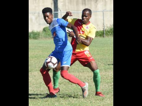 Shai Smith (left) of Portmore United shields the ball from Humble Lion's Levaughn Williams  during their Red Stripe Premier League match at the Spanish Town Prison Oval on January 5, 2020.