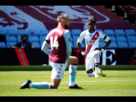 Crystal Palace's Wilfried Zaha takes a knee in support of the Black Lives Matter movement before the English Premier League match between Aston Villa and Crystal Palace at Villa Park in Birmingham, England, Sunday, July 12, 2020.
