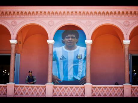 A giant poster of Diego Maradona is displayed on a balcony of the presidential palace known as the Casa Rosada or Pink House, in Buenos Aires, Argentina, yesterday.
