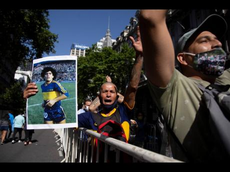 A man holds a poster of Diego Maradona when he played for the football club Boca Juniors, as he waits in a line outside the presidential palace to pay his last respects, in Buenos Aires, Argentina, yesterday.