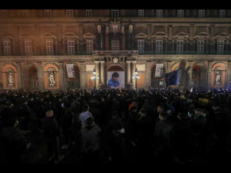 A photo of football legend Diego Maradona is hanging from Naples' Royal Palace in the central Piazza Plebiscito, as football fans gathered to commemorate him yesterday.